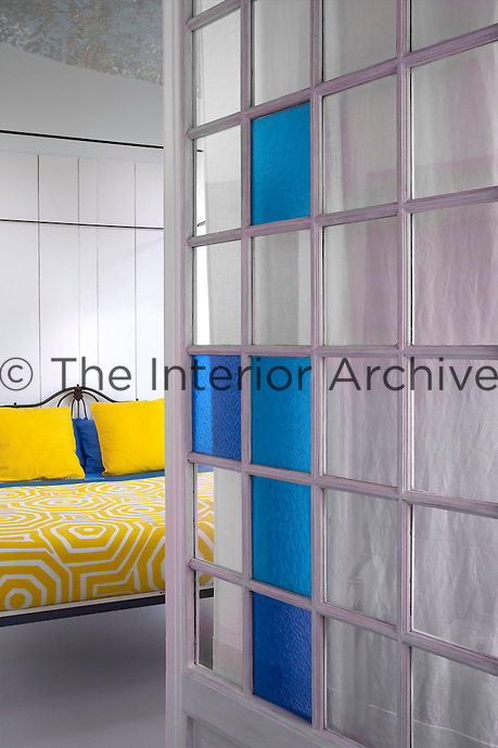 View past the pivotal glass door from the ensuite bathroom into the simple bedroom