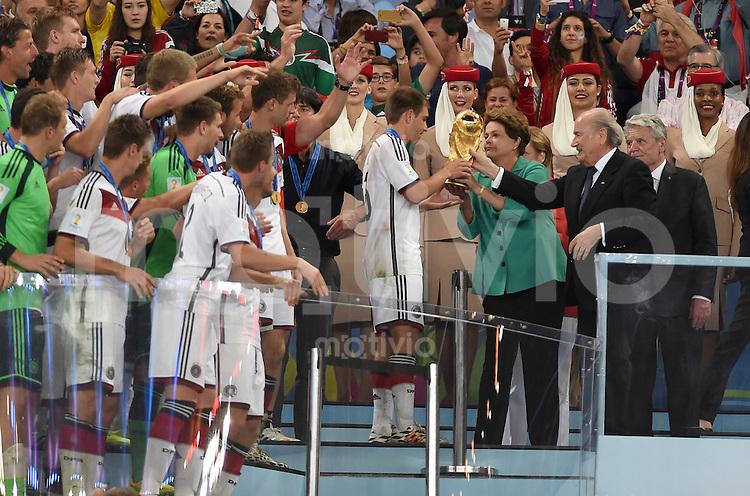 FUSSBALL WM 2014                       FINALE   Deutschland - Argentinien     13.07.2014 DEUTSCHLAND FEIERT DEN WM TITEL: Joseph S. Blatter ueberreicht unter den Augen von Bundespraesident Joachim Gauck (re) an Philipp Lahm (li) den WM Pokal