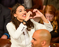 United States Representative Alexandria Ocasio-Cortez (Democrat of New York) sends a message with a sign of a heart to someone in the gallery as the 116th Congress convenes for its opening session in the US House Chamber of the US Capitol in Washington, DC on Thursday, January 3, 2019. Photo Credit: Ron Sachs/CNP/AdMedia