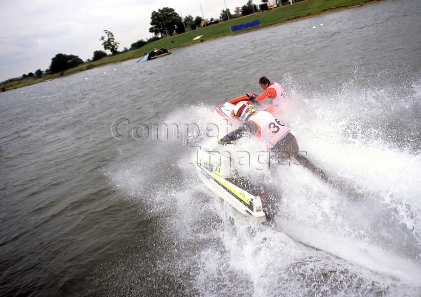 Two Jet ski riders race along river