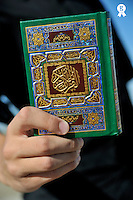 Hand showing Koran book cover (Licence this image exclusively with Getty: http://www.gettyimages.com/detail/83154251 )