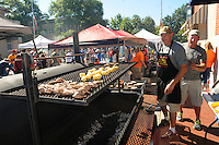 """NWA Democrat-Gazette/FLIP PUTTHOFF <br /> TREE CUISINE<br /> Jeff Pollock (left) and David Mitchell fix smoked squirrel with corn on the cob  Saturday Sept. 12 2015 during the third annual World Championship Squirrel Cookoff in downtown Bentonville. Teams of squirrel chefs prepared an array of dishes with squirrel meat, such as gumbo, meatballs and stuffed peppers. The team """"Bud and Bones"""" comprised of Jeff Terry of Pea Ridge, Dan Judd of Rogers and Tim Owens of Bella Vista won the cookoff with their dish, empanadas with spanish cream rice. Money raised at the event benefited Sheep Dog Impact Assistance, which aids military and law enforcement personnel, said Joe Wilson, cookoff chief."""