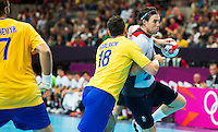 31 JUL 2012 - LONDON, GBR - Steven  Larsson (GBR) of Great Britain (right) looks for a way through Sweden's defence during the men's London 2012 Olympic Games Preliminary round match at The Copper Box in the Olympic Park, in Stratford, London, Great Britain (PHOTO (C) 2012 NIGEL FARROW)
