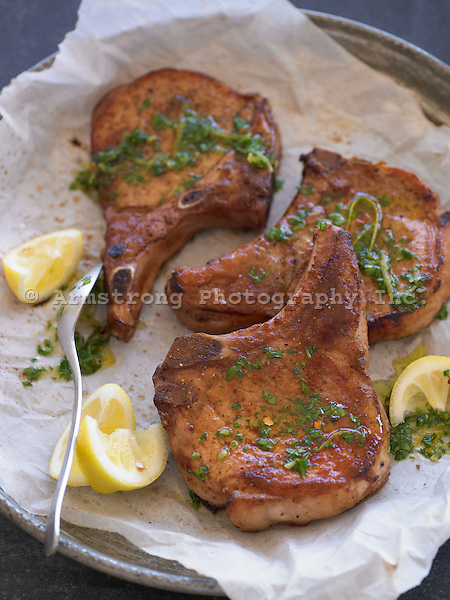 Platter of pork chops with Moroccan pesto and lemon slices