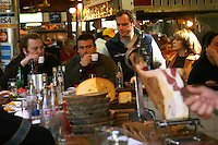 People sitting at the bar drinking and eating at lunch time on a Sunday, in the restaurant El Palenque, the sword fish swordfish, in the Mercado del Puerto, the market in the port harbour harbor where many people go and eat and shop on weekends Montevideo, Uruguay, South America