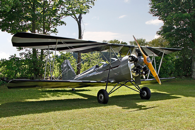 A silver-bodied, Meyers OTW (out-to-win) bi-plane with black and white striped wings rests on the grass, bearing its shadow, backed by a blue sky and trees at the 2010 Wings 'n' Wheels Showcase.