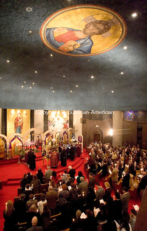 WATERBURY, CT-17 APRIL 2009 --041709JS10--Parishioners stand with candles lit as The Very Reverend Dr. Stephen P. Natsis, pastor of Holy Trinity Greek Orthodox Church in Waterbury leads The Lamentation Service and Holy Procession for the Eastern Orthodox Good Friday service at the church on Friday. While Western chuches observed Good Friday and Easter last week, the Eastern Orthodox Church follows the rules set down by the First Ecumenical Council of Nicaea in 325 A.D.<br /> Jim Shannon Republican-American