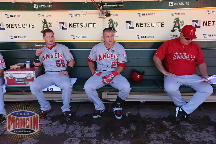 OAKLAND, CA - SEPTEMBER 18:  Kole Calhoun #56, Mike Trout #27, and manager Mike Scioscia #14 of the Los Angeles Angels get ready in the dugout before the game against the Oakland Athletics at O.co Coliseum on Wednesday, September 18, 2013 in Oakland, California. Photo by Brad Mangin