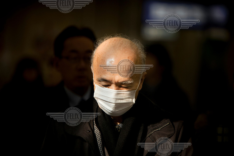 A commuter, wearing a surgical mask, at Shibuya station during the morning rush hour.
