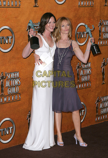 JORJA FOX & MARG HELGENBERGER.11th Annual Screen Actors Guild Awards (SAG) held at the Shrine Auditorium. Los Angeles, California.Photo Credit: Jacqui Wong/AdMedia.February 5th, 2005.full length award trophy purple dress chiffon sheer white dress, long gold silver chain necklace arm around waist .www.capitalpictures.com.sales@capitalpictures.com.© Capital Pictures.
