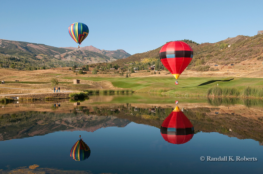 Hot air balloons soar over landscape at Snowmass Balloon Festival, Colorado.