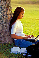 Young female student uses a laptop while she leans against a tree.