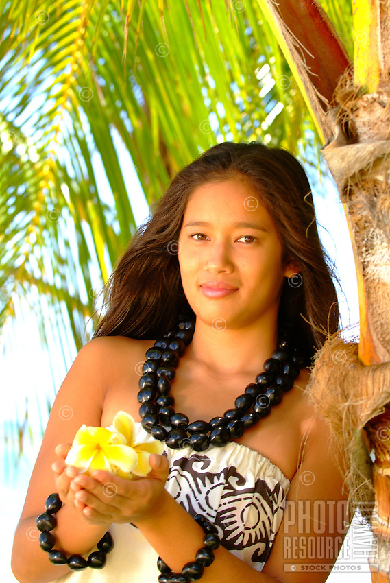 Young woman with plumeria and kukui nut adornments