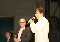 Actor & film maker Jackie Chan (R)  get on stage with World Film Festival's President  Serge Losique (L) for the free outdoor  projection of one of Chan's movie `. at the 25th World Film Festival,Sept 1st 2001 in Montreal, CANADA.<br /> <br /> Apprenticed to the Peking Opera by his parents at the age of 6, Jackie Chan was rigorously trained in music, dance, and traditional martial arts. A visiting filmmaker offered Chan his first (tiny) role as a stunt player. Chan took the part, and soon left the Opera to pursue the world of film. Fellow Opera students Biao Yuen and Sammo Hung Kam-Bo would also have careers in film, and the three would star in several films together in the following years. Chan's talent and enthusiasm soon saw him taking larger and more important roles, graduating first to stunt coordinator, and then to director. <br /> <br /> <br /> <br /> Following the death of martial arts legend Bruce Lee, the search was on for an actor who could inspire audiences to the same degree; every young martial artist was given a chance. Chan decided that rather than emulating Lee (and thus living forever in his shadow), he would develop his own style of filmmaking. His directorial debut Shi di chu ma (1980) was a milestone in martial arts films, being the first to effectively combine comedy with action. This set the tone for many of his future films, which combined slapstick humor with high-energy martial arts action. A self-confessed fan of Buster Keaton and Harold Lloyd, Chan performs all his own stunts, quite often at his own peril. His later films include outtakes of his on-set injuries run under the closing credits. He is the world number one in his field<br /> <br /> <br /> <br />  <br /> <br /> Photo by John Raudsepp (Transmited & paid to Pierre Roussel)<br /> <br /> NOTE : raw jpeg from Nikon D 1, openened with QUIMAGE ICC profile