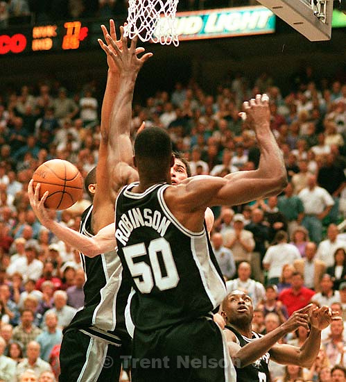 John Stockton drives between Tim Duncan and David Robinson at Utah Jazz vs. San Antonio Spurs, game 2, 2nd round, NBA Playoffs.<br />