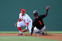 Outfielder Gregory Lorenzo (1) of the Delmarva Shorebirds steals second base, with Mookie Betts of the Greenville Drive defending in a game on Monday, April 29, 2013, at Fluor Field at the West End in Greenville, South Carolina. Lorenzo is listed as the No. 29 prospect of the Baltimore Orioles, according to Baseball America. Delmarva won, 6-5. (Tom Priddy/Four Seam Images)