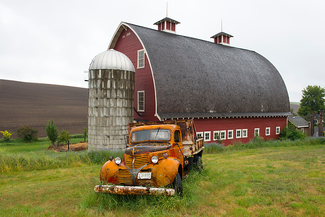 Old truck in front of red barn in the Palouse near Colfax, Eastern Washington State, USA.