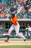 Henry Urrutia (51) of the Norfolk Tides follows through on his swing against the Charlotte Knights at BB&T BallPark on April 9, 2015 in Charlotte, North Carolina.  The Knights defeated the Tides 6-3.   (Brian Westerholt/Four Seam Images)