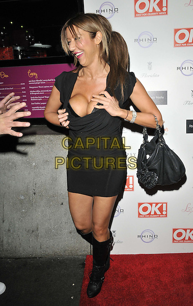 Sally Anne Jones.The OK! magazine Christmas party, Floridita London bar & restaurant, Wardour St., London, England..November 29th, 2011.full length black boots dress cleavage hand bag purse hands pushing squeezing funny profile reaching .CAP/CAN.©Can Nguyen/Capital Pictures.