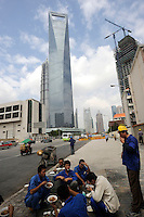 Chinese workers have lunch in front of Shanghai World Financial Center in Pudong, Shanghai, China..