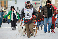 Musher Cim Smyth leads his dogs to the start line on 4th avenue during the Ceremonial Start of the 2016 Iditarod in Anchorage, Alaska.  March 05, 2016