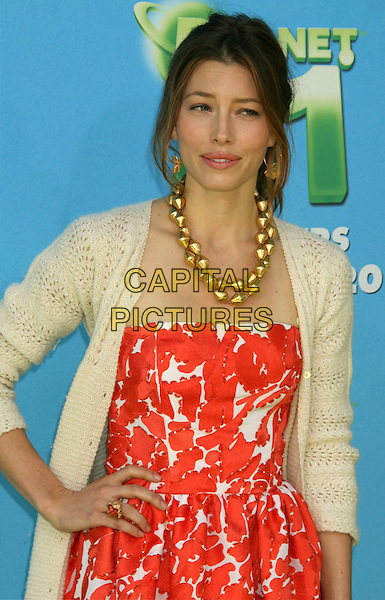 """JESSICA BIEL.At The Premiere of Columbia Pictures """"Planet 51"""" held at The Mann Village Theatre, Westwood, California, USA, 14th November 2009..half length hand on hip red orange and white print pattern beige cream knitted pointelle cardigan chunky gold necklace dress .CAP/ADM/MJ.©Michael Jade/AdMedia/Capital Pictures."""