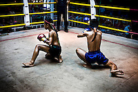 Keng (black short pants) is performing the ritual dance called  Wai khru ram muay before fighting. Keng is a 12 years old kid, and he has fighted over 70 times, he has been champion in Chiang Mai, and is reconized in several boxing circles around the city. His father passed away when he was 7 years old, and now help his mother earning half of  the income that she is getting per month each time he fight. For them there is not other way. He is going by the hand of his mother to each combat. Shy and reserved is holding his dream to reach the big Bangkok  competitions in future.