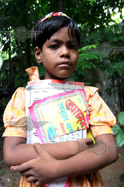 A young student from Gree village school holding her textbooks.