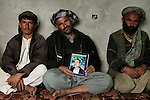Afghan brothers Najibullah, Azizbullah, and Bismellah pose with a photograph of a fourth brother Obaidullah in their home in the northern Afghan town of Imam Sahib in Kunduz Province on Tuesday April 15, 2009. Obaidullah - a driver for the town's mayor - was killed along with four other men in night raid by US special forces on March 22, 2009. US military press releases describe the men killed as militants and claim four other high-level targets were detained in the operation but family-members and townspeople claim they were simple workers and that no one was taken from the home in the raid.