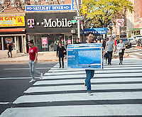 A consumer carries his Samsung UHD television across an intersection in New York on Sunday, October 30, 2016. The cost of 4K televisions has come down precipitously making them the great hope of retailers as the hot holiday item. (© Richard B. Levine)