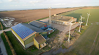 Rural farm buildings with, solar panels, wind turbines and mobile telephone mast - Norfolk, February