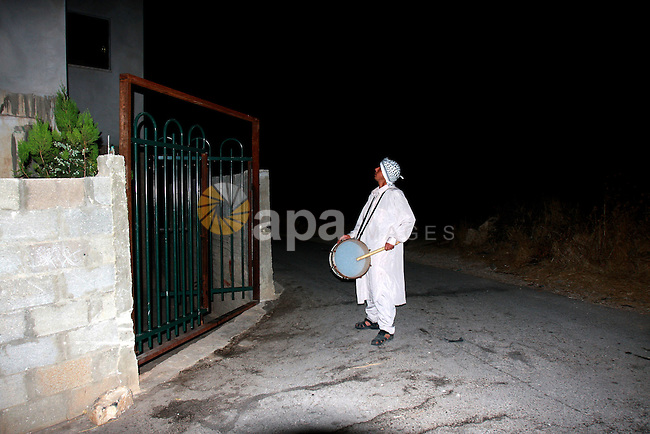 A Palestinian man 'Mesaharaty' uses a traditional drum to wake up people for their Suhoor, in the village of Balata in the West Bank city of Nablus, on, Aug .18, 2011. Muslims throughout the world are celebrating the holy fasting month of Ramadan, the holiest month in Islamic calendar, refraining from eating, drinking, and smoking from dawn to dusk. Photo by Wagdi Eshtayah