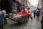 A man pushes a cart with fish up the old market street of Qingdao. The street was built during the German occupation.