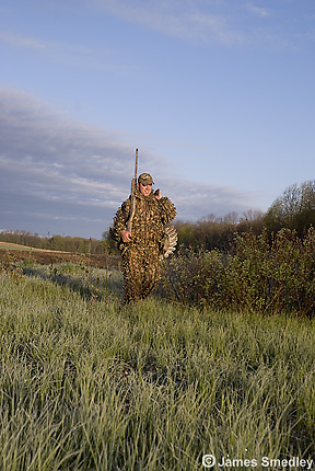 Hunter with wild turkey over his shoulder