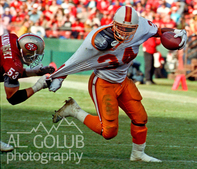 San Francisco 49ers vs. Tampa Bay Buccaneers at Candlestick Park Saturday, December 19, 1992.  49ers Beat Buccaneers 21-14.  San Francisco 49ers linebacker Bill Romanowski (53) pulls down Tampa Bay Buccaneers running back Reggie Cobb (34).  .