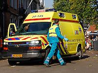 Ambulancemedewerker loopt naast een ambulance