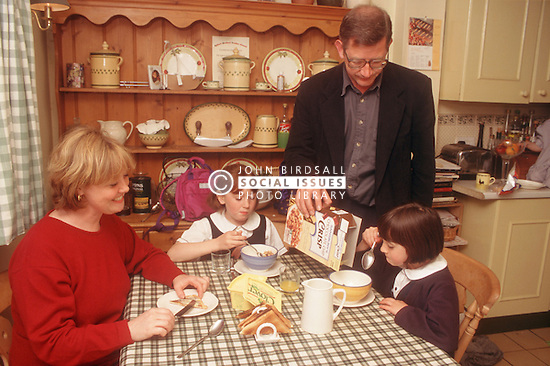 Couple and two young daughters eating breakfast at kitchen table,