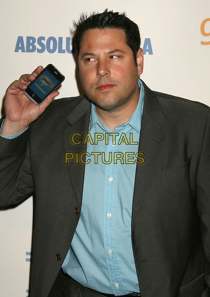GREG GRUNBERG.20th Annual GLAAD Media Awards held at the Nokia Theatre, Los Angeles, California, USA..April 18th, 2009.half length suit grey gray jacket iphone mobile phone blue shirt funny .CAP/ADM/MJ.©Michael Jade/AdMedia/Capital Pictures.