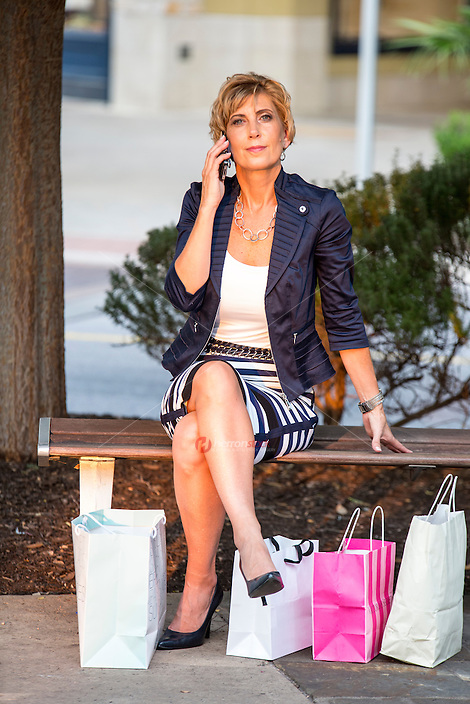 Attractive female shopper takes a call on her mobile smartphone at an Austin outdoor shopping mall