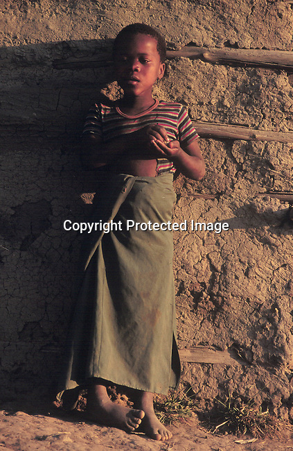 PPCHILD50293 Young girl with ragged clothing standing agains a mud wall  in Kwa-Zulu Natal 99.©Per-Anders Petterson/iAfrika Photos