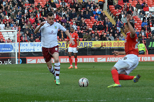 22.03.2014 London, England. Burnley striker Sam Vokes skips a challenge from Jordan Cousins during the Championship game between Charlton Athletic and Burnley from The Valley.