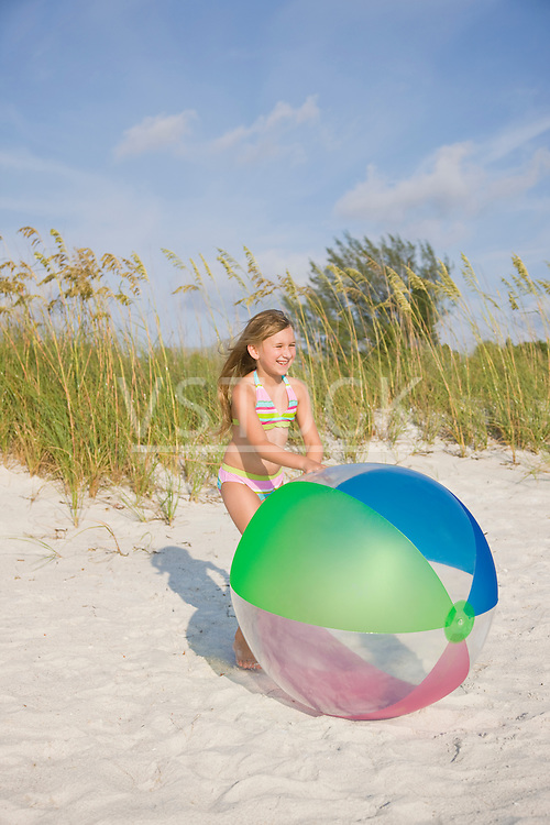 USA, Florida, St. Pete Beach, Girl (8-9) playing with large colorful ball on beach