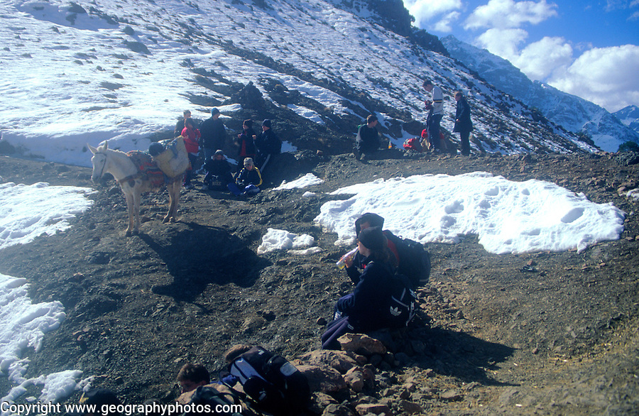 School students rest at high mountain pass on trek in Atlas Mountains, Morocco