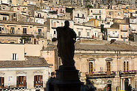 The late Baroque town of Modica in Sicily is divided into a lower section, which is crammed into a snaking valley, and a higher section, which has many warren-like narrow lanes, but there are many fine churches in both. This view is from the steps of one of these churches looking out at the houses of the lower town.