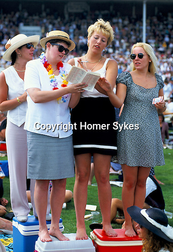 YOUNG LADIES STUDYING RACING GUIDE AT ASCOT RACES,