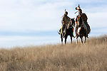 Two Native American Indian men on horseback scouting for enemies in the prairie of South Dakota