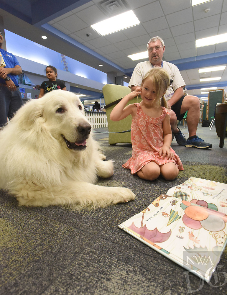 NWA Democrat-Gazette/FLIP PUTTHOFF <br /> FURRY READING PAL<br /> Rosemary Jonasson, 4, shows a picture book on Saturday July 6 2019 to Obi, a certified therapy dog, at the Rogers Public Library. Larry Gramling (seated) of Centerton brought the great pyrenees dog to the library for children to pet and read books to Obi. Gramling and Obi make regular appearances at libraries, shelters and other locales including Northwest Arkansas Regional Airport. Obi lets passengers stroke his soft fur and helps soothe passengers who may be stressed.