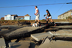 Brandon and Lila Clements walk their terrier Sam past a section of beachfront road destroyed by Hurricane Isabel at Kitty Hawk.