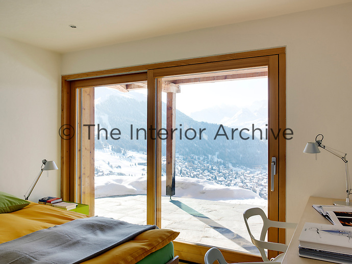 Sliding glass doors open onto a paved terrace from one of the guest bedrooms, with spectacular views over Verbier