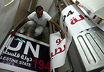 """A Palestinian worker inspects a banner as it prints in the West Bank city of Ramallah September 13, 2011. A grass-root campaign supporting the upcoming Palestinian bid at the United Nations is gearing up for the diplomatic showdown at the United Nations later this month when Palestinian President Mahmoud Abbas is expected to seek an upgrade of the Palestinians' U.N. status. The Palestinians hope to establish a state in the Gaza Strip and the Israeli-occupied West Bank, with Arab East Jerusalem as their capital. The banner reads: """"The People want membership of a Palestinian state at the UN"""". Photo by Issam Rimawi"""